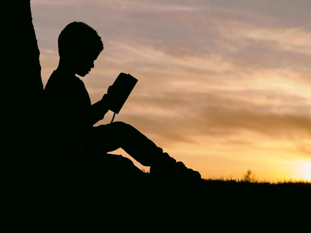 Silhouette of a child reading. Photo by Aaron Burden on Unsplash