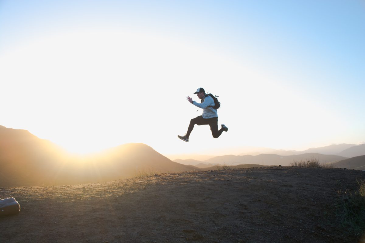 Photo of a man jumping at sunrise by Cam Adams