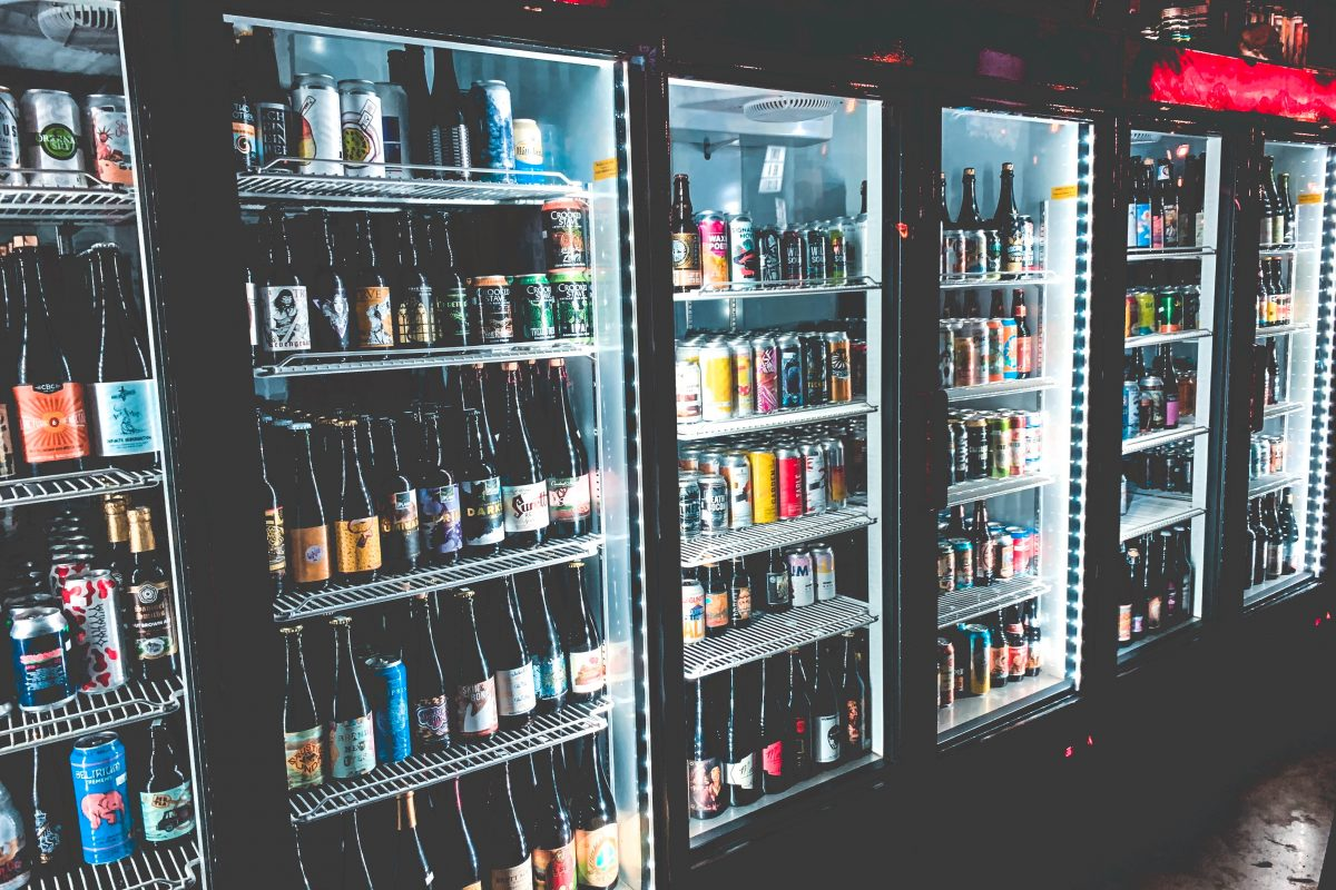 A photo of fridges filled with drinks. Photo by Justin Sanchez on Unsplash