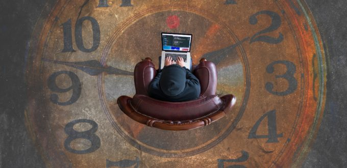 A picture of a man working on a computer in the middle of a clock face