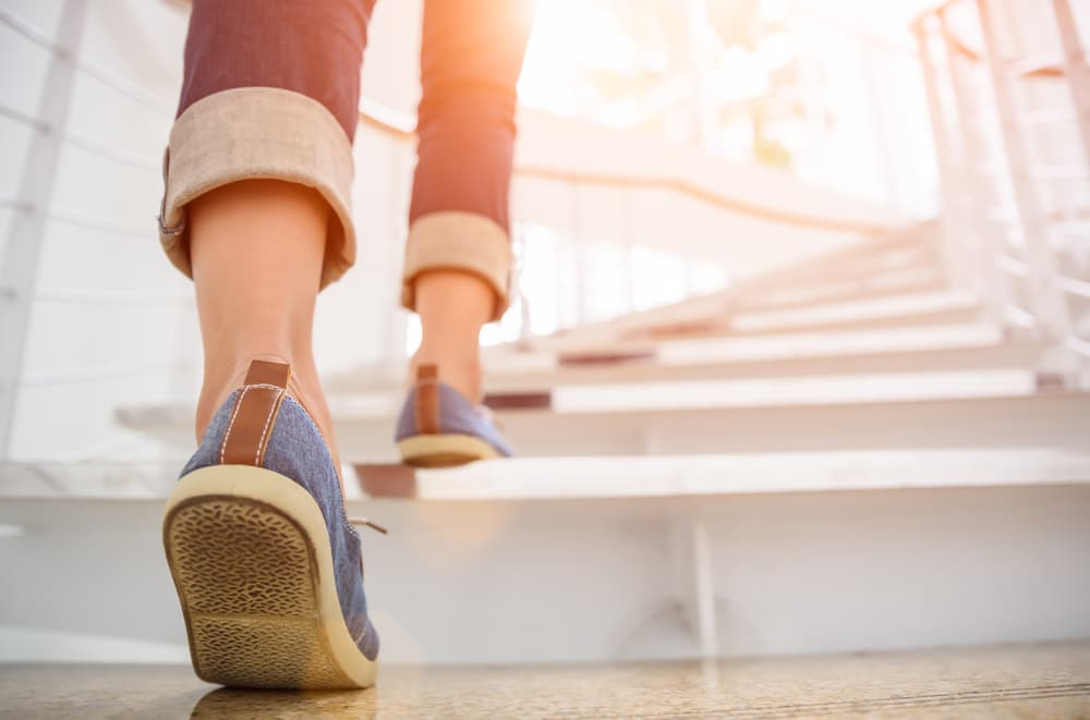 A woman walking up steps (Pic: Shutterstock)