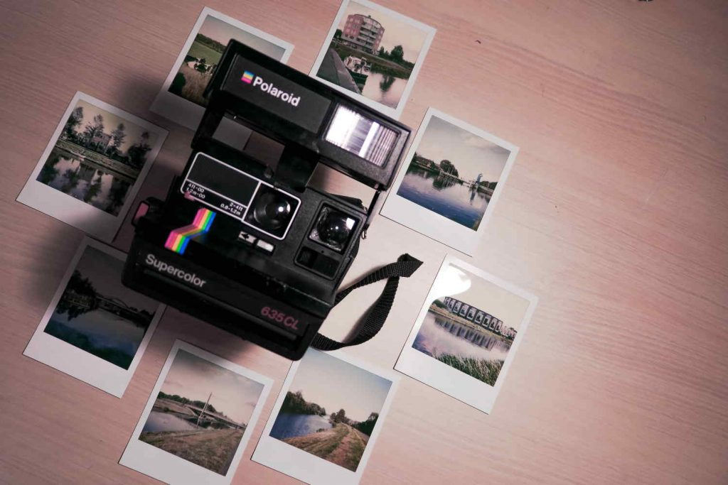 Photos around a polaroid camera. Photo by Denise Jans on Unsplash.