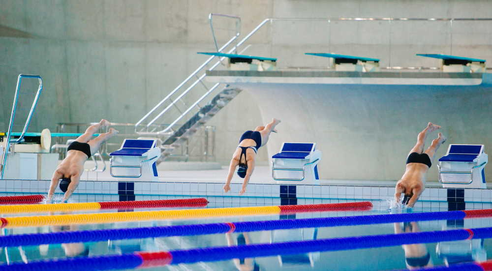 A photo of swimmers jumping into the pool at the London Aquatics Centre. Photo by Dylan Nolte on Unsplash