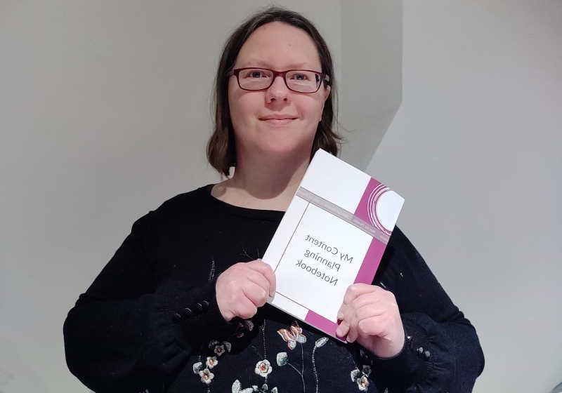 Rachel Extance holding My Content Planning Notebook
