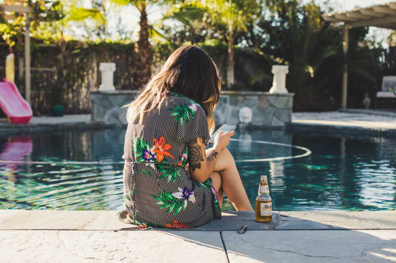 A woman sitting by a pool reading on her phone. Photo by Kvnga on Unsplash