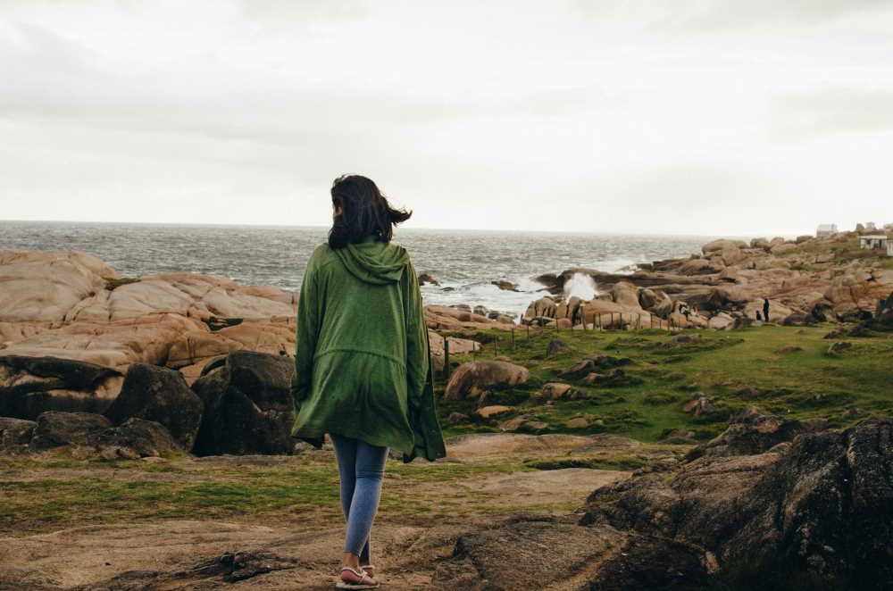 Woman walking by the sea. Photo by Paz Arando on Unsplash