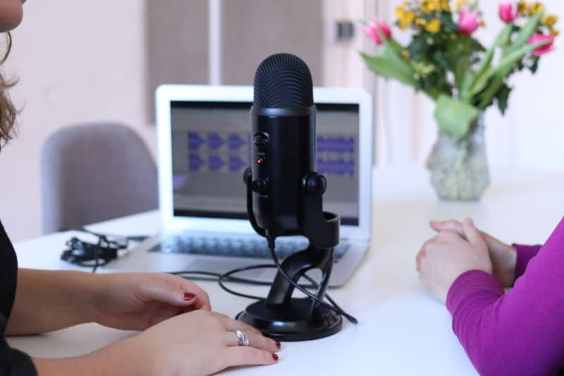 Two people recording a podcast with a microphone. Photo by CoWomen on Unsplash