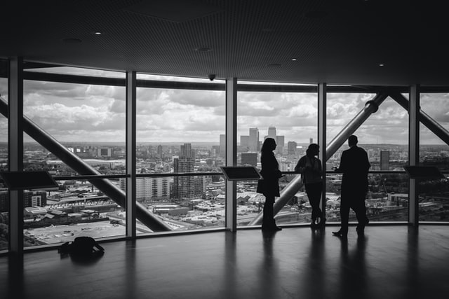 A black and white photo of three people meeting in a big room with glass windows overlooking a city. Photo by Charles Forerunner on Unsplash