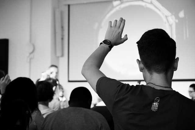 A black and white photo of a student raising their hand in class, taken from the back of the room. Photo by Felicia Buitenwerf on Unsplash