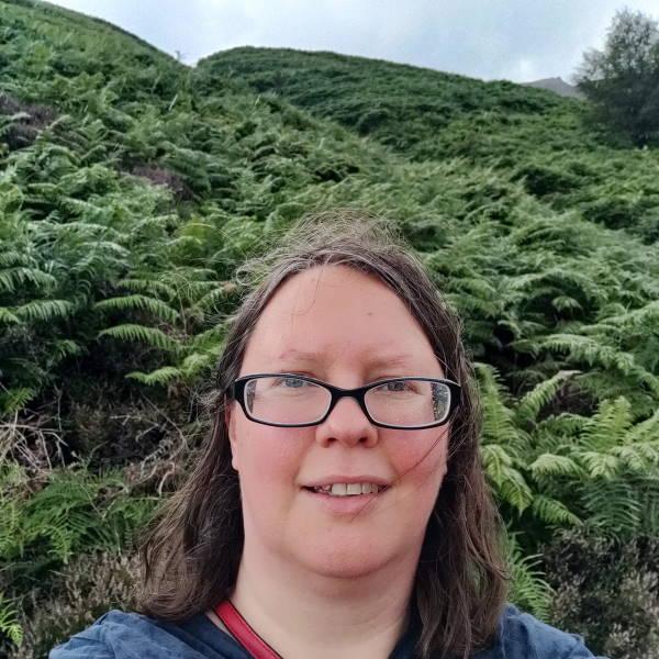 A photo of Rachel walking in the rain in Edale